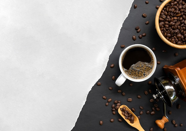 Tasse kaffee, weißes papier und bohne auf schwarzem holztischhintergrund. draufsicht Premium Fotos