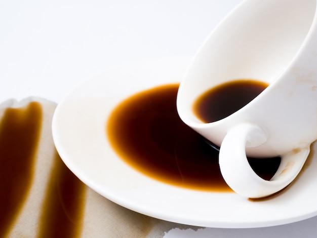 Tasse kaffee wurde auf weißem hintergrund, draufsicht verschüttet. für grunge reklameanzeigeauslegung kopieren sie platz Premium Fotos