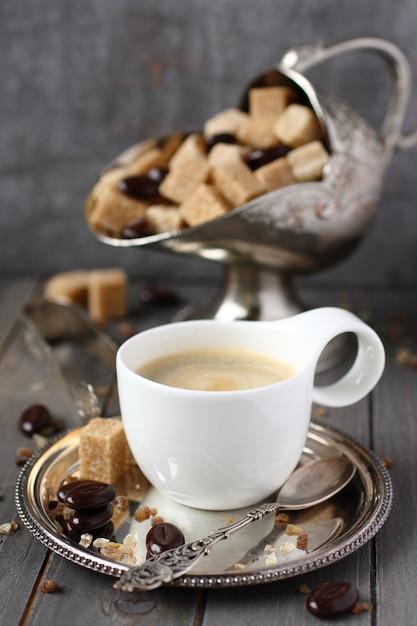 Tasse kaffee, zuckerwürfel und praline auf altem hölzernem hintergrund Premium Fotos