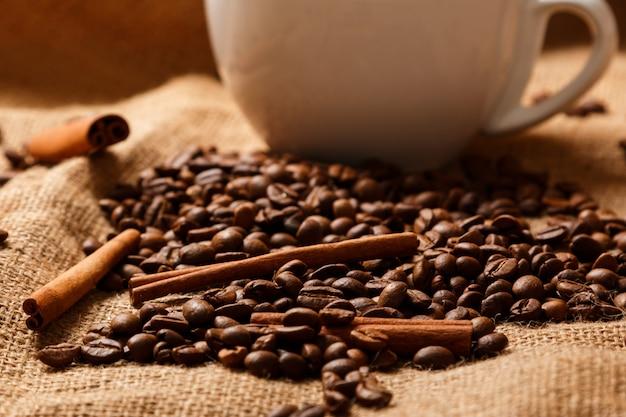 Tasse, kaffeebohnen und zimtstangen Premium Fotos