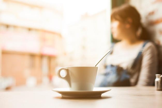 Tasse kaffeetasse vor der defocus frau, die weg schaut Kostenlose Fotos
