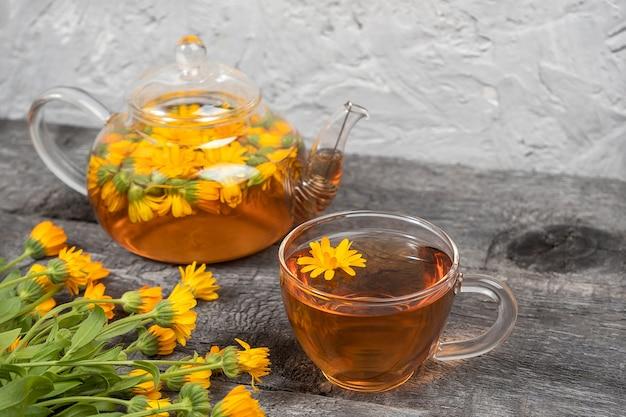 Tasse kräutertee und transparente teekanne und ringelblumenblumen auf holzhintergrund. calendula tea kommt ihrem gesundheitskonzept zugute. Premium Fotos
