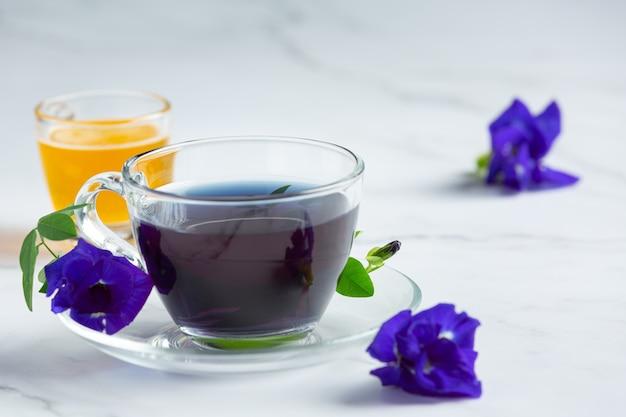 Tasse schmetterlingserbsenblumentee mit honig auf tisch Kostenlose Fotos