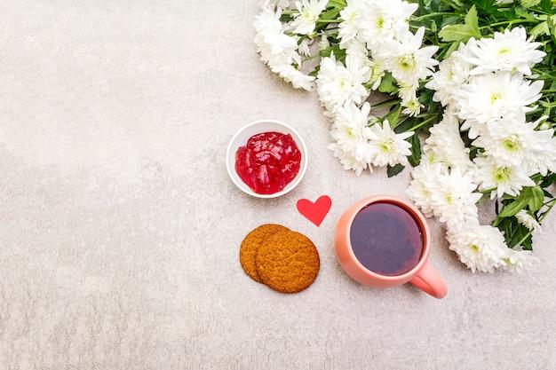 Tasse schwarzen tee, haferkekse, kirschgelee und bouquet von chrysanthemen Premium Fotos