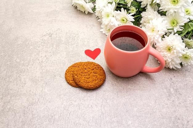Tasse schwarzen tee, haferkekse und bouquet von chrysanthemen Premium Fotos