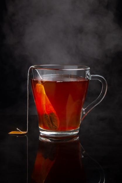 Tasse schwarzen tee mit dampf auf einem dunklen Premium Fotos