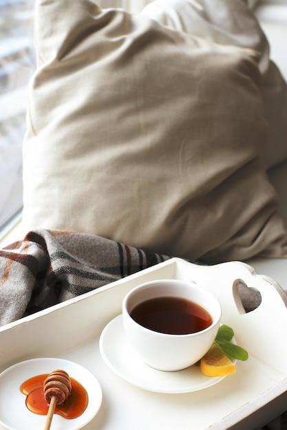 Tasse tee auf dem bett Kostenlose Fotos