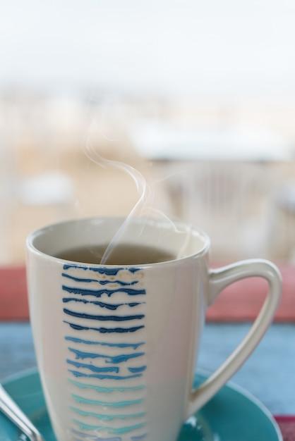 Tasse tee auf vintage holztisch mit unscharfem meeresstrand Premium Fotos