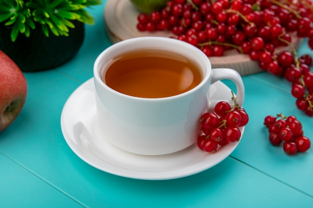 Tasse tee der seitenansicht mit roten johannisbeeren mit äpfeln auf hellblauem hintergrund Kostenlose Fotos