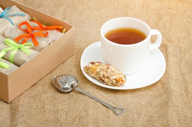 Tasse tee, eine stange müsli und kisten mit stangen. sackleinen Premium Fotos