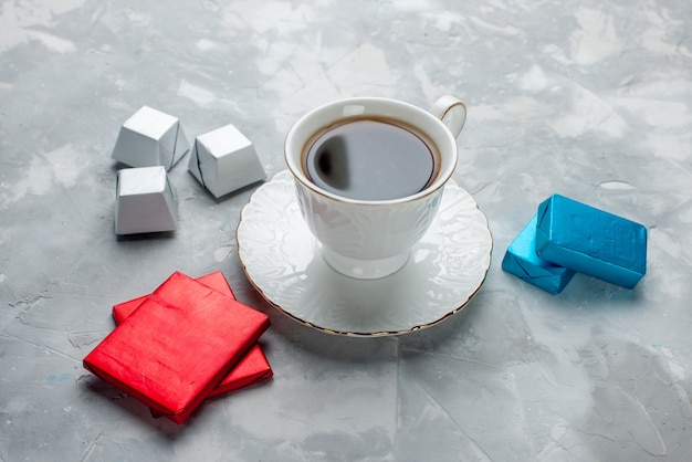 Tasse tee heiß in weißer tasse auf glasplatte mit silber anded paket pralinen auf hellem schreibtisch, tee trinken süße kekse teatime Kostenlose Fotos