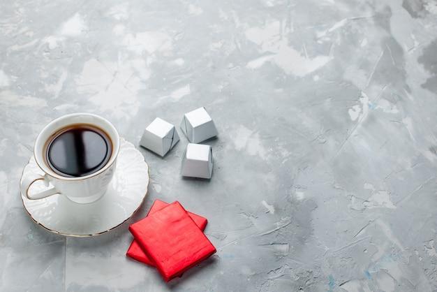 Tasse tee heiß in weißer tasse auf glasplatte mit silberverpackung pralinen auf hellem schreibtisch, tee trinken süße schokolade keks teatime Kostenlose Fotos
