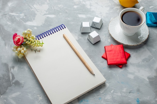 Tasse tee heiß in weißer tasse mit silber anded paket pralinen notizblock auf hellen schreibtisch, trinken süße kekse teatime Kostenlose Fotos