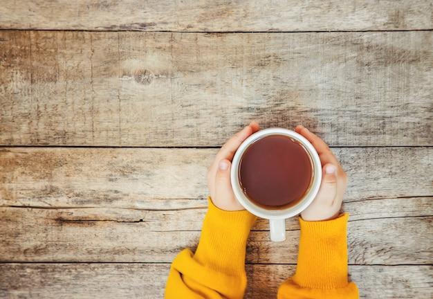 Tasse tee in den händen eines kindes und ein gemütlicher herbsthintergrund. selektiver fokus Premium Fotos