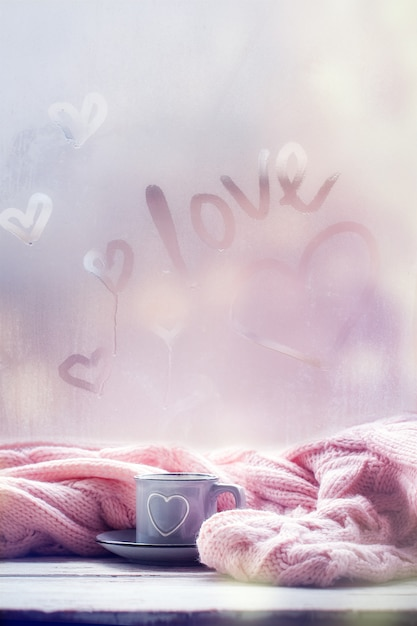 Tasse tee, kaffee, schokolade und rosa plaid auf nebeligem fenster mit liebestext. liebe stimmung. hygge-konzept. Premium Fotos