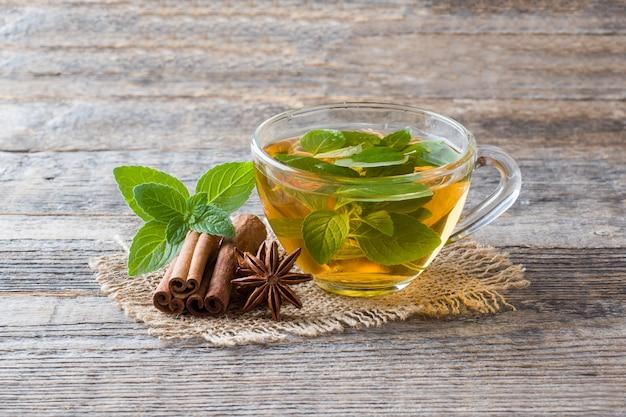 Tasse tee mit frischen tadellosen blättern und zimtanis auf holz Premium Fotos