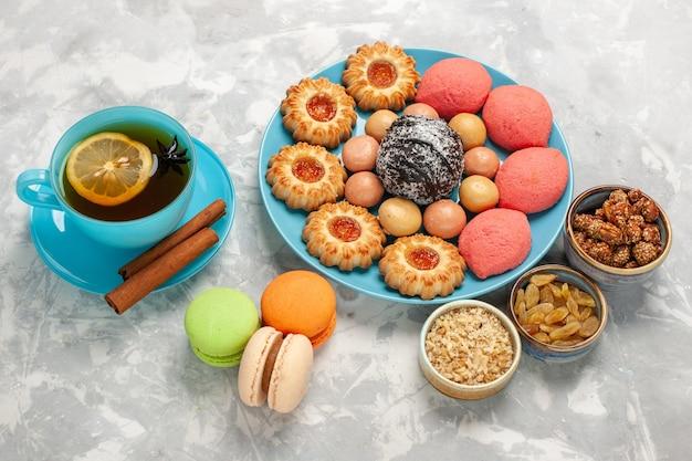 Tasse tee mit halber draufsicht mit keksen und kuchen von french macarons auf weißer oberfläche Kostenlose Fotos