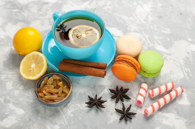 Tasse tee mit halber draufsicht mit macarons und rosinen auf der weißen oberfläche Kostenlose Fotos