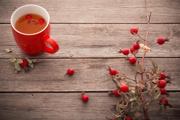 Tasse tee mit hippen rosen, auf holztisch Premium Fotos