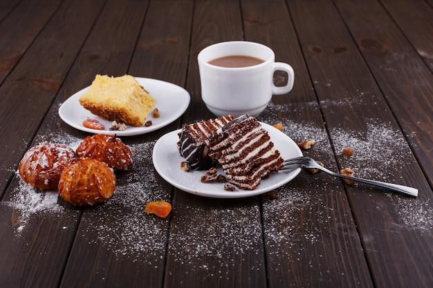 Tasse tee mit milch und zwei platten mit käsekuchen und schokoladenkuchen Kostenlose Fotos