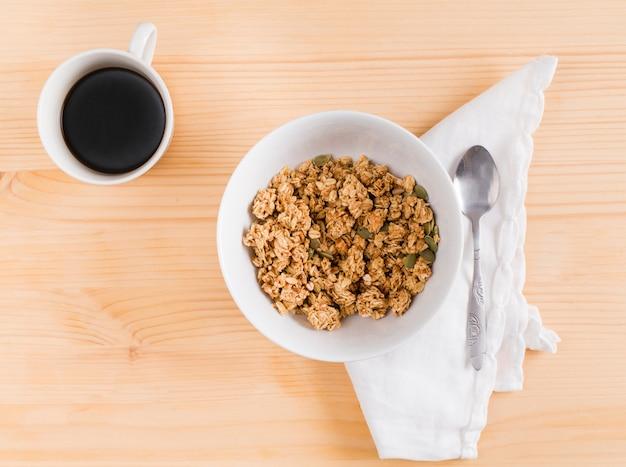 Tasse tee mit weißer schüssel granola- und kürbiskernen auf hölzernem schreibtisch Kostenlose Fotos