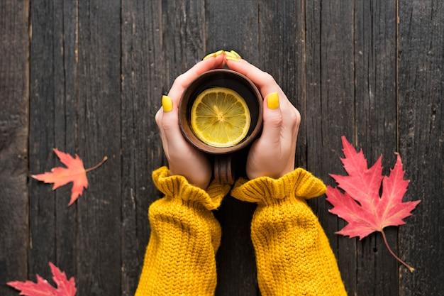 Tasse tee mit zitrone in einer weiblichen hand. herbstblätter. ansicht von oben Premium Fotos