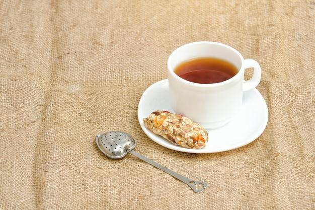 Tasse tee, müsliriegel und teesieb auf sackleinen Premium Fotos