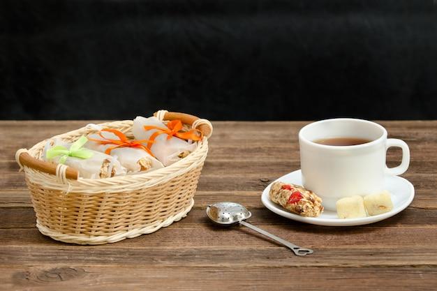 Tasse tee, müsliriegel und teesieb. weidenkorb mit bars. brown aus holz Premium Fotos