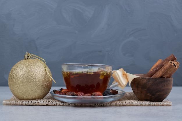 Tasse tee, schüssel zimtstangen und festliche kugel auf weißem tisch. Kostenlose Fotos