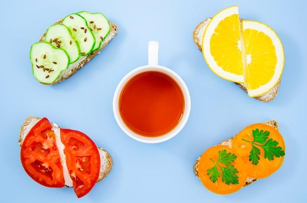 Tasse tee, umgeben von verschiedenen sandwiches Kostenlose Fotos