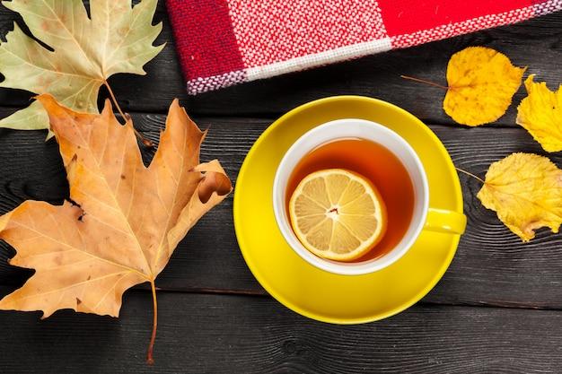 Tasse tee und herbstlaub auf dem tisch Premium Fotos