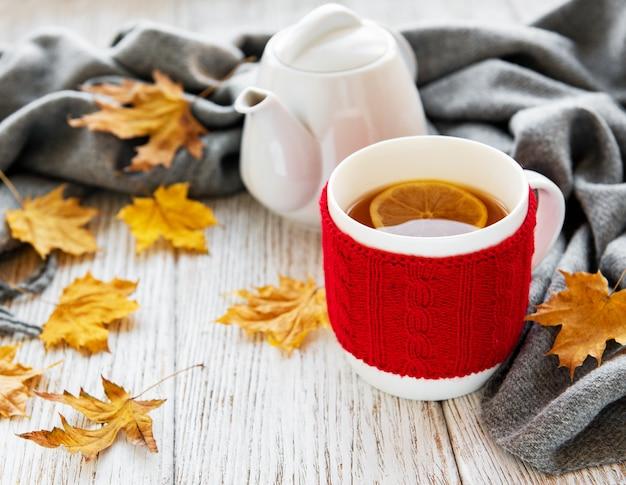 Tasse tee und herbstlaub Premium Fotos