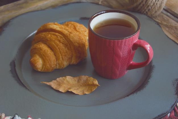 Tasse tee und hörnchen der französischen frühstückszusammensetzung der herbststimmung Premium Fotos