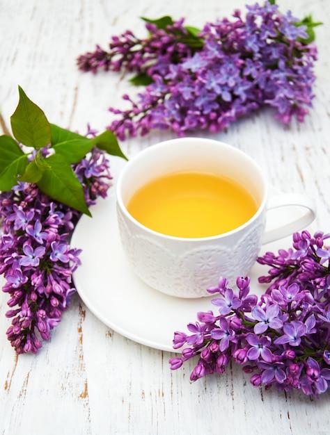 Tasse tee und lila blumen Premium Fotos