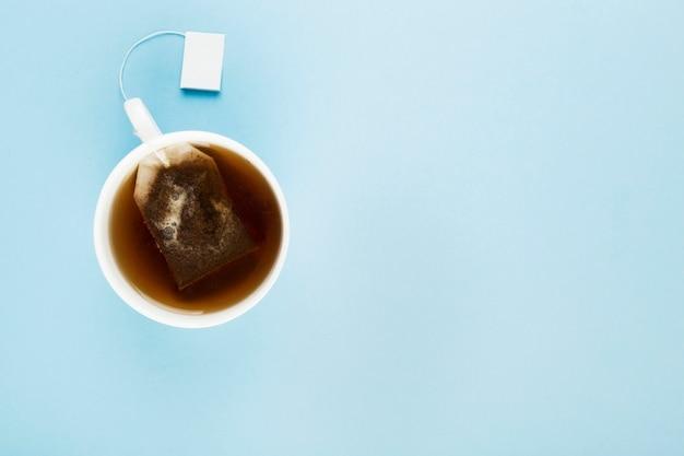 Tasse tee und teebeutel auf blauem hintergrund. draufsicht, kopie, raum Premium Fotos