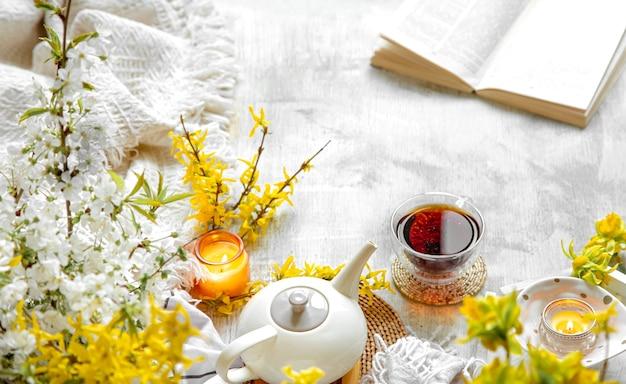 Tasse tee und teekanne zwischen frühlingsblumen und brennenden kerzen Premium Fotos