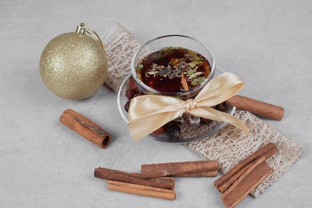Tasse tee, zimtstangen und festliche kugel auf weißem tisch. hochwertiges foto Kostenlose Fotos