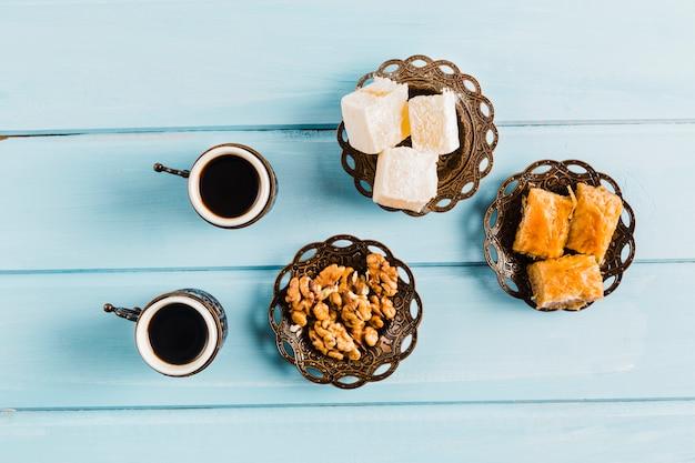 Tassen kaffee in der nähe von untertassen mit süßen türkischen desserts Kostenlose Fotos