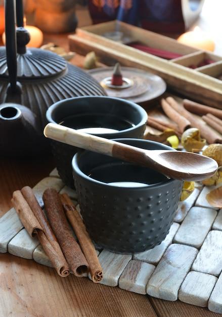 Tassen schwarzer tee begleitet von weihrauch, zimt und kerzen Premium Fotos