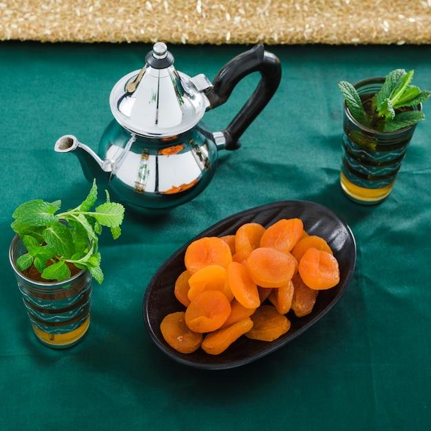 Tassen trinken in der nähe von teekanne und getrockneten aprikosen Kostenlose Fotos