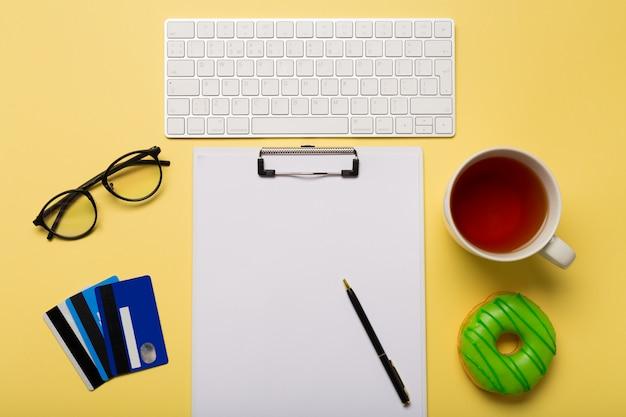Tastatur, tasse tee, kreditkarten, papier und stift auf gelbem hintergrund. Premium Fotos