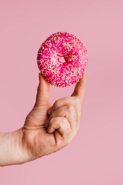 Tasty donut mit hellen belag in der hand Kostenlose Fotos