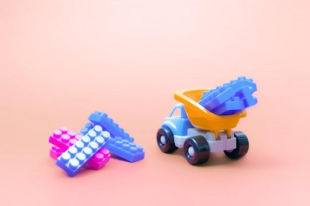 Tauschen sie spielzeugmodellauto mit blöcken des erbauers auf rosa hintergrund Premium Fotos