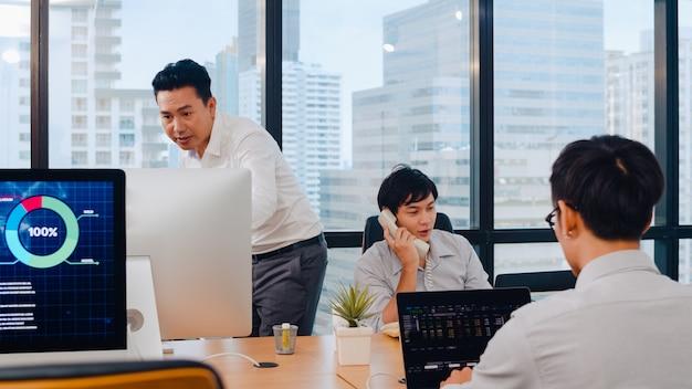 Tausendjährige gruppe junger asiatischer geschäftsleute in einem kleinen modernen büro. japanischer männlicher chef supervisor unterrichtet praktikant oder neuer mitarbeiter chinesischer junger mann, der bei schwieriger aufgabe im besprechungsraum hilft. Kostenlose Fotos