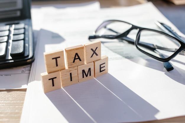 Tax time-holzbuchstaben mit steuerformular, brille und taschenrechner Premium Fotos