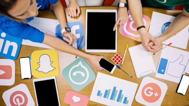 Team mit social media icons und elektronisches gadget über den tisch Kostenlose Fotos