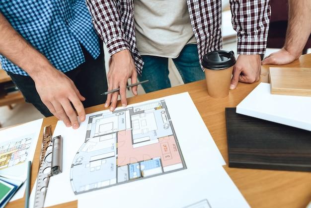 Team von designerarchitekten betrachten grundriss. Premium Fotos