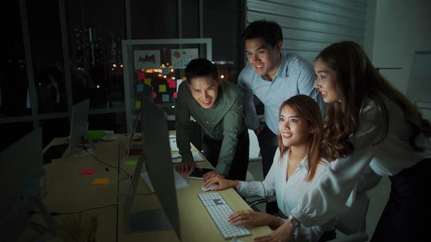 Team von diversity-geschäftsleuten, die spät im büro nachts arbeiten. zwei kaukasische männer und asiatische mädchen fühlen sich glücklich und erfolgreich für neue geschäfte. arbeiten spät in der nacht und überstunden konzept Premium Fotos