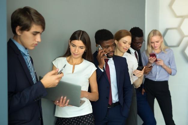 Team von jungen schönen menschen im büro mit handys Premium Fotos