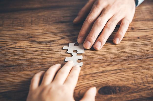 Teamhände, die puzzle auf schreibtisch halten Premium Fotos